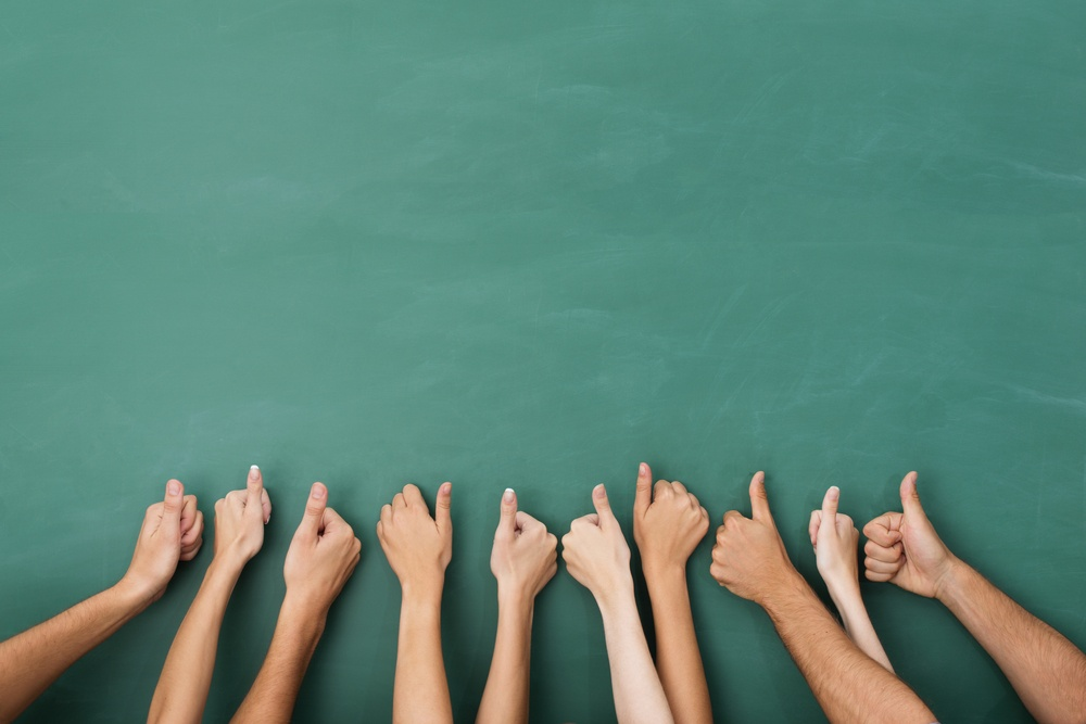 Close up view of the hands of a group of people giving a thumbs up gesture of approval an success with their hands raised against a blank green chalkboard with copyspace.jpeg